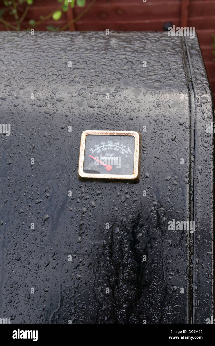 wet rain soaked BBQ temperature guage clock reading zero - Stock Image