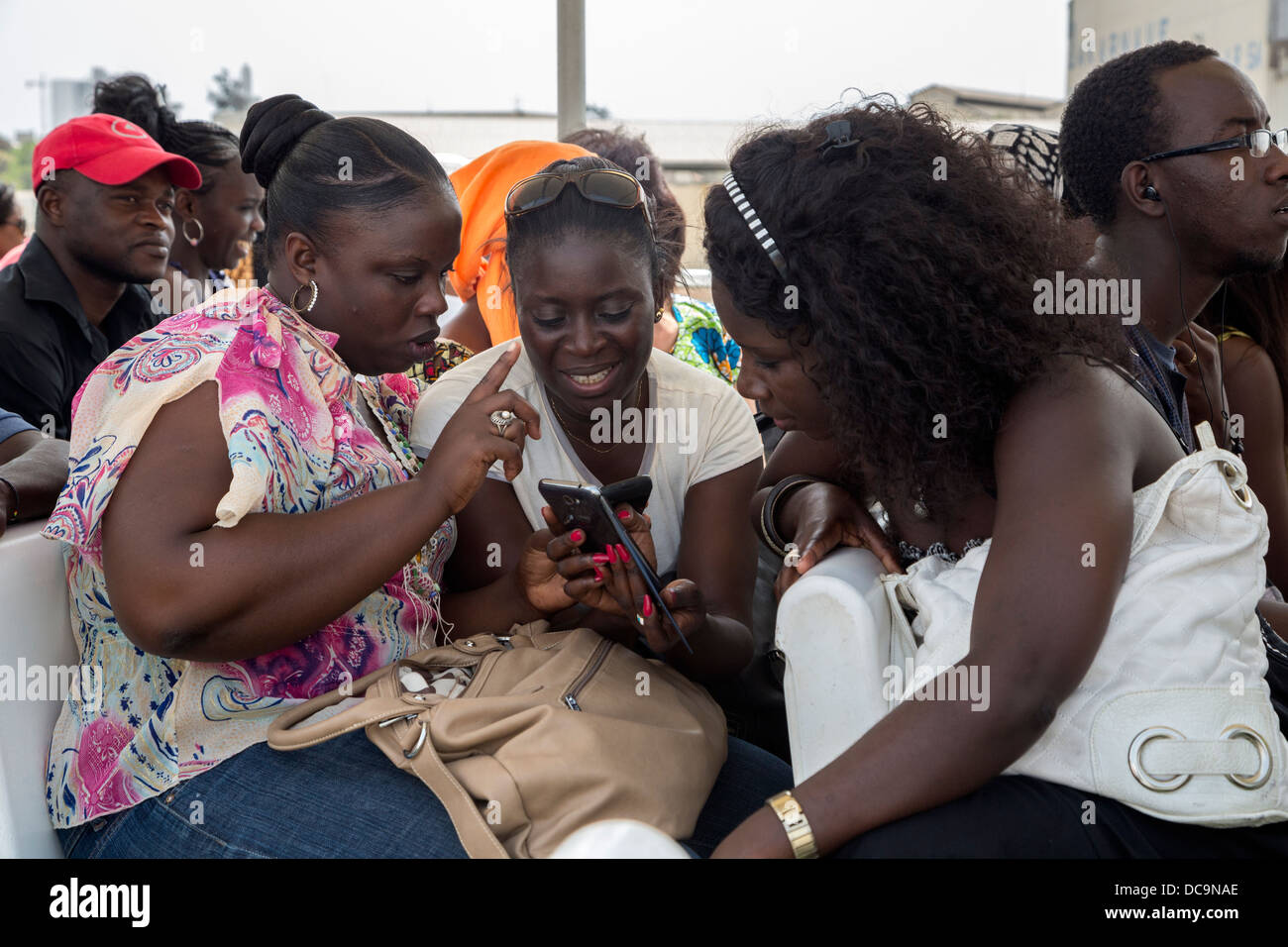 Passengers Looking at Cell Phone Pictures on the Dakar-Goree Ferry, Senegal. - Stock Image