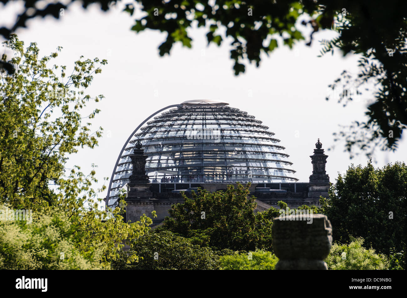 The Reichstag Dome, designed by the architect Sir Norman Foster, framed by trees - Berlin Germany Stock Photo