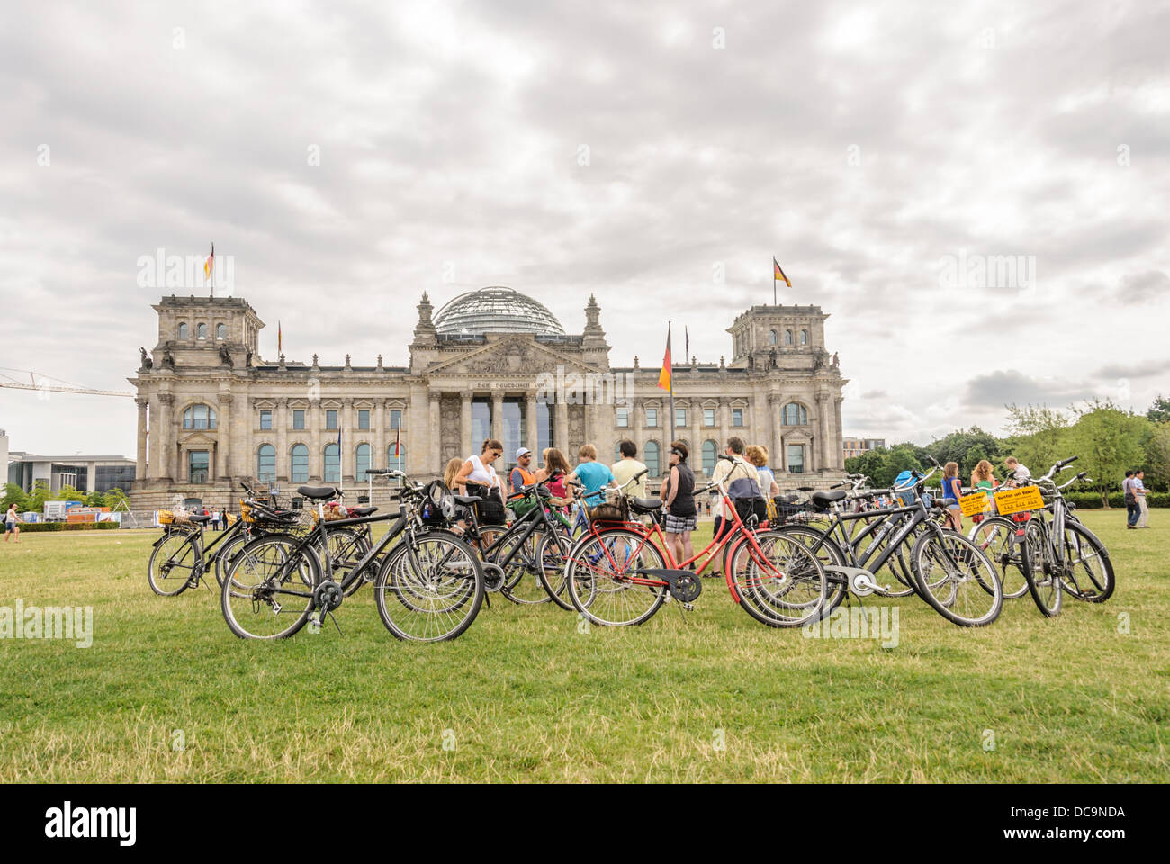 Berlin on Bike - Sightseeing tourists group with bicycles in front of the Reichstag building - Berlin Germany Stock Photo