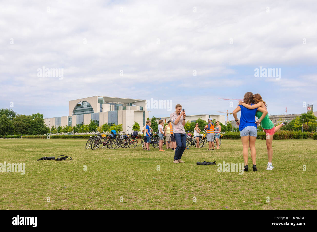 2 young women posing for young man taking pictures in front of the Chancellery and a group of bicycle tourists Stock Photo