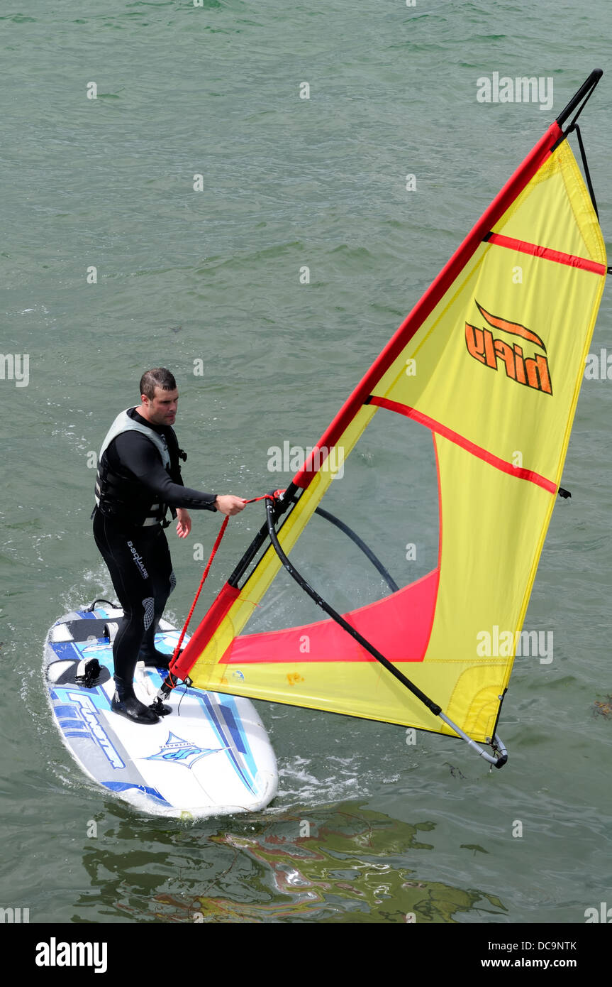 Close-up of a man on a white sailboard with yellow sail on the sea near Anstruther, Fife, Scotland, UK - Stock Image