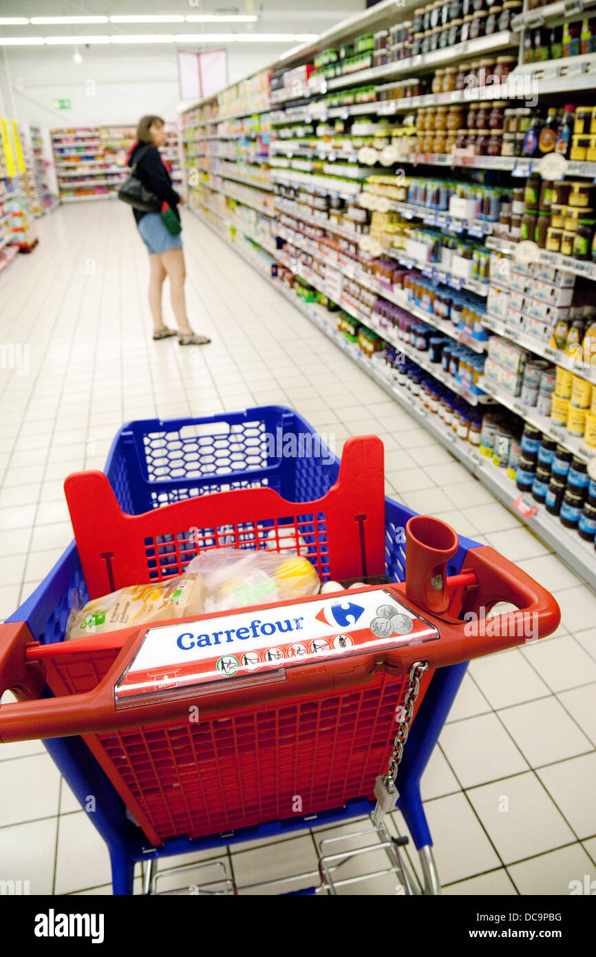 A woman shopping for food in Carrefour french supermarket, with her trolley in the aisle, the dordogne, France Europe - Stock Image