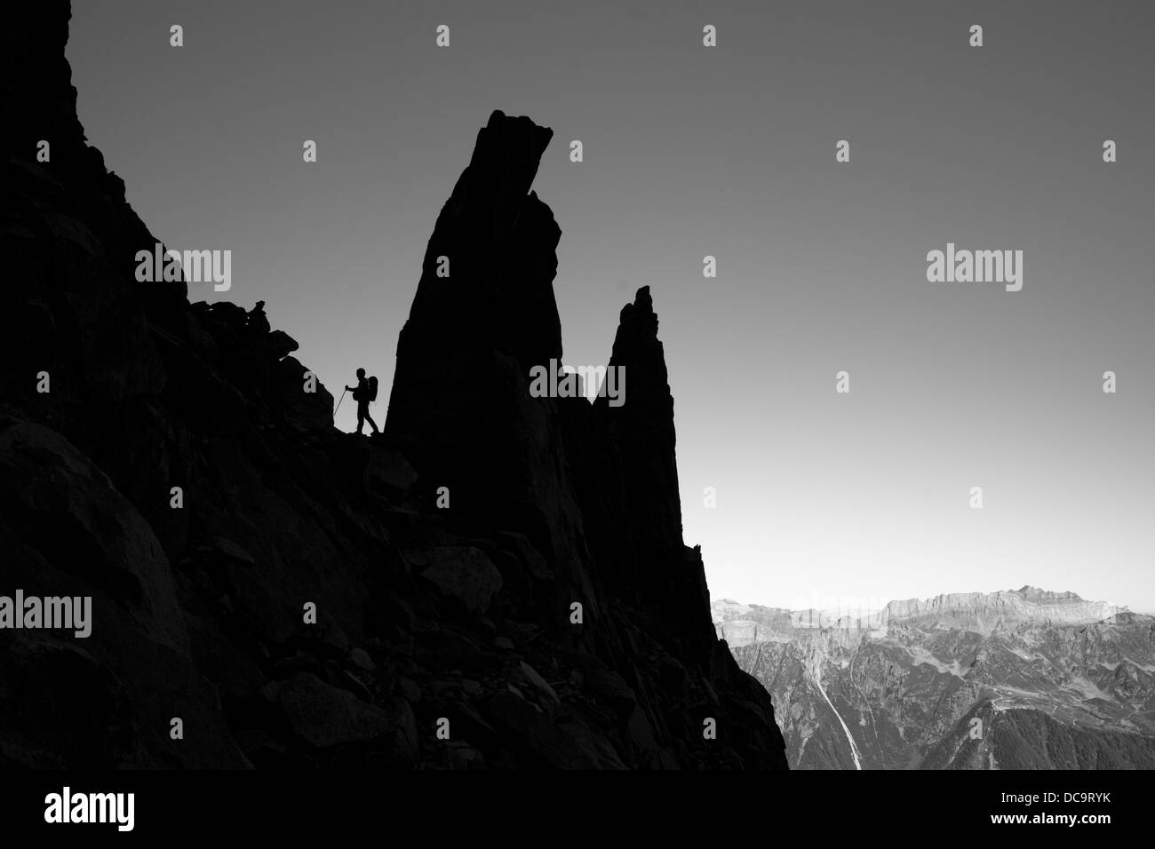 Side view on mountaineer, climber, silhouette on the ridge in mountain scenery. - Stock Image