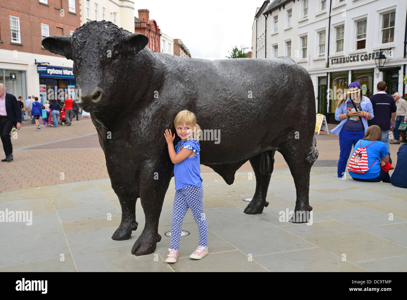Child by bronze Hereford Bull statue, High Street, High Town, Hereford, Herefordshire, England, United Kingdom - Stock Image