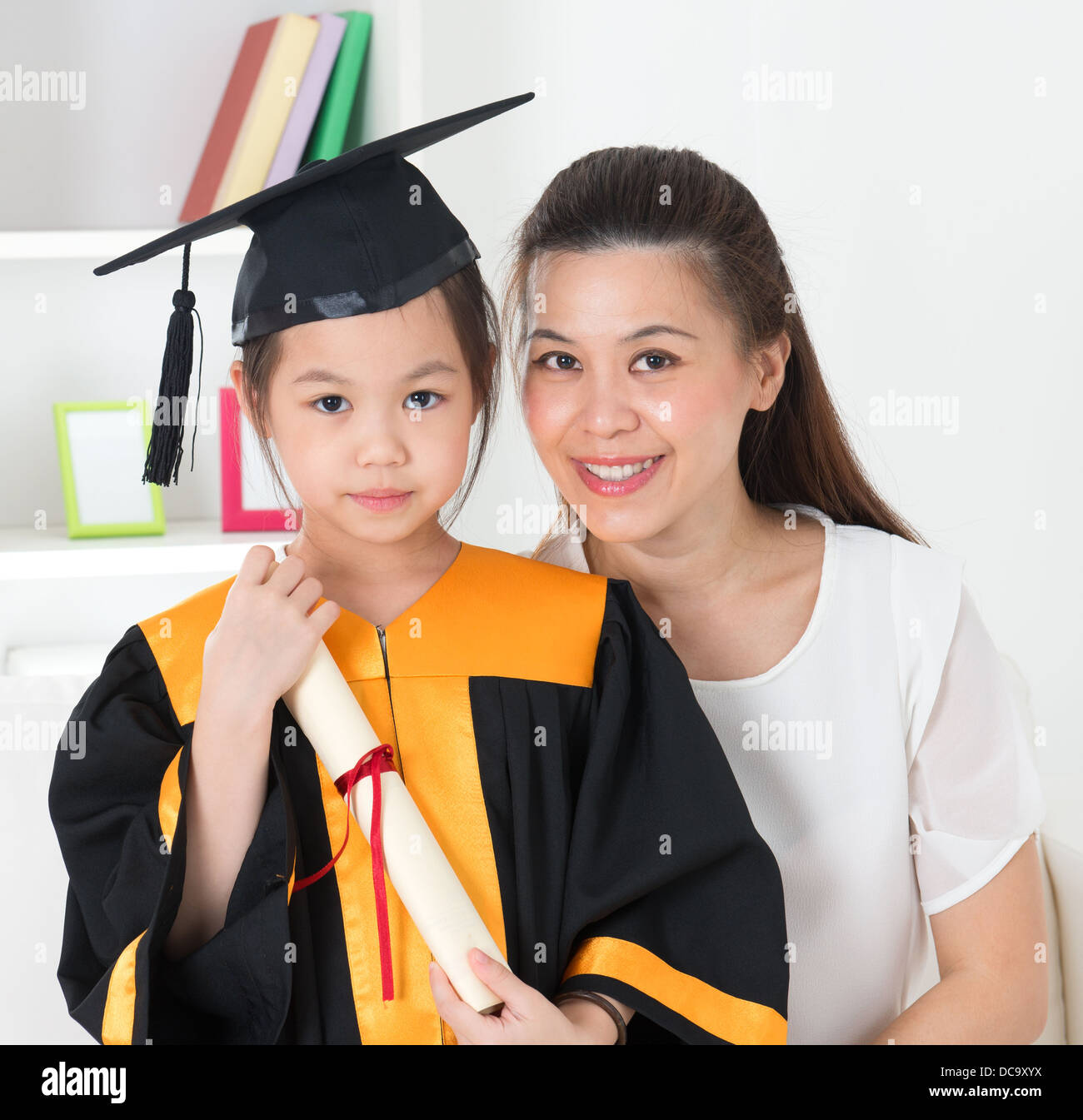 Asian school kid graduate in graduation gown and cap. Taking photo ...