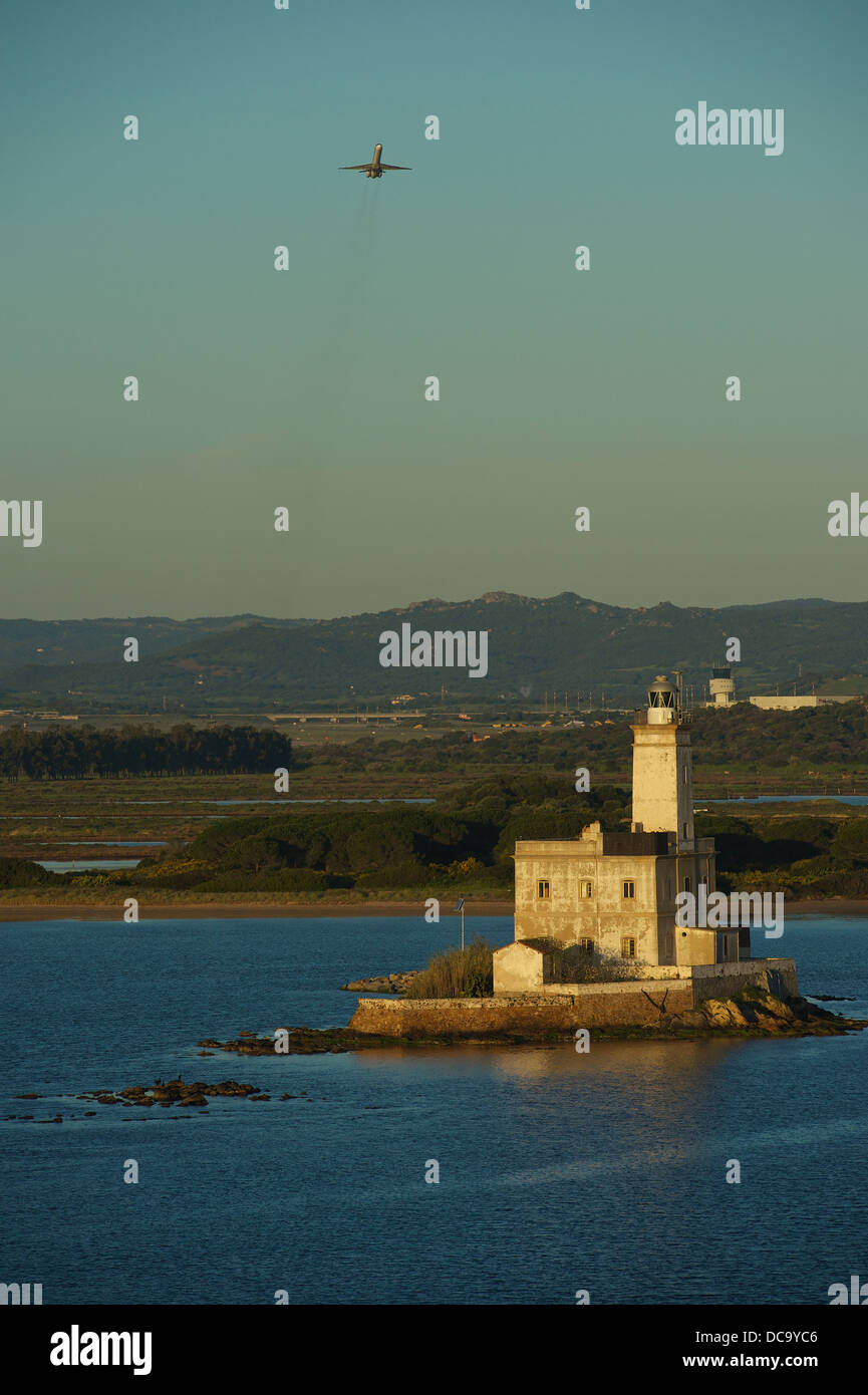 Approaching the Port of Olbia with the ferry boat. Lighthouse of Olbia with airplane taking off from the airport - Stock Image
