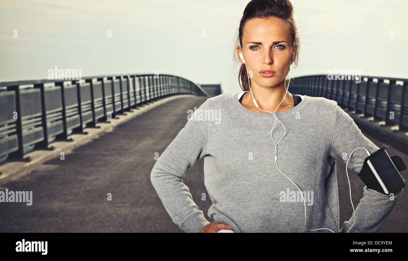 Serious female jogger outdoors looking confident - Stock Image