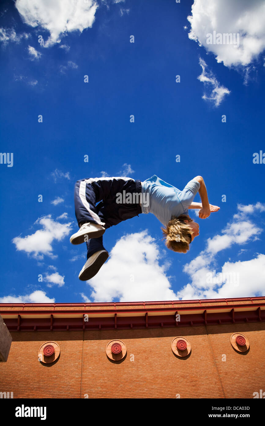 Teenage Parkour athlete in mid-air during a daring backflip. Slight motion blur on the athlete. - Stock Image