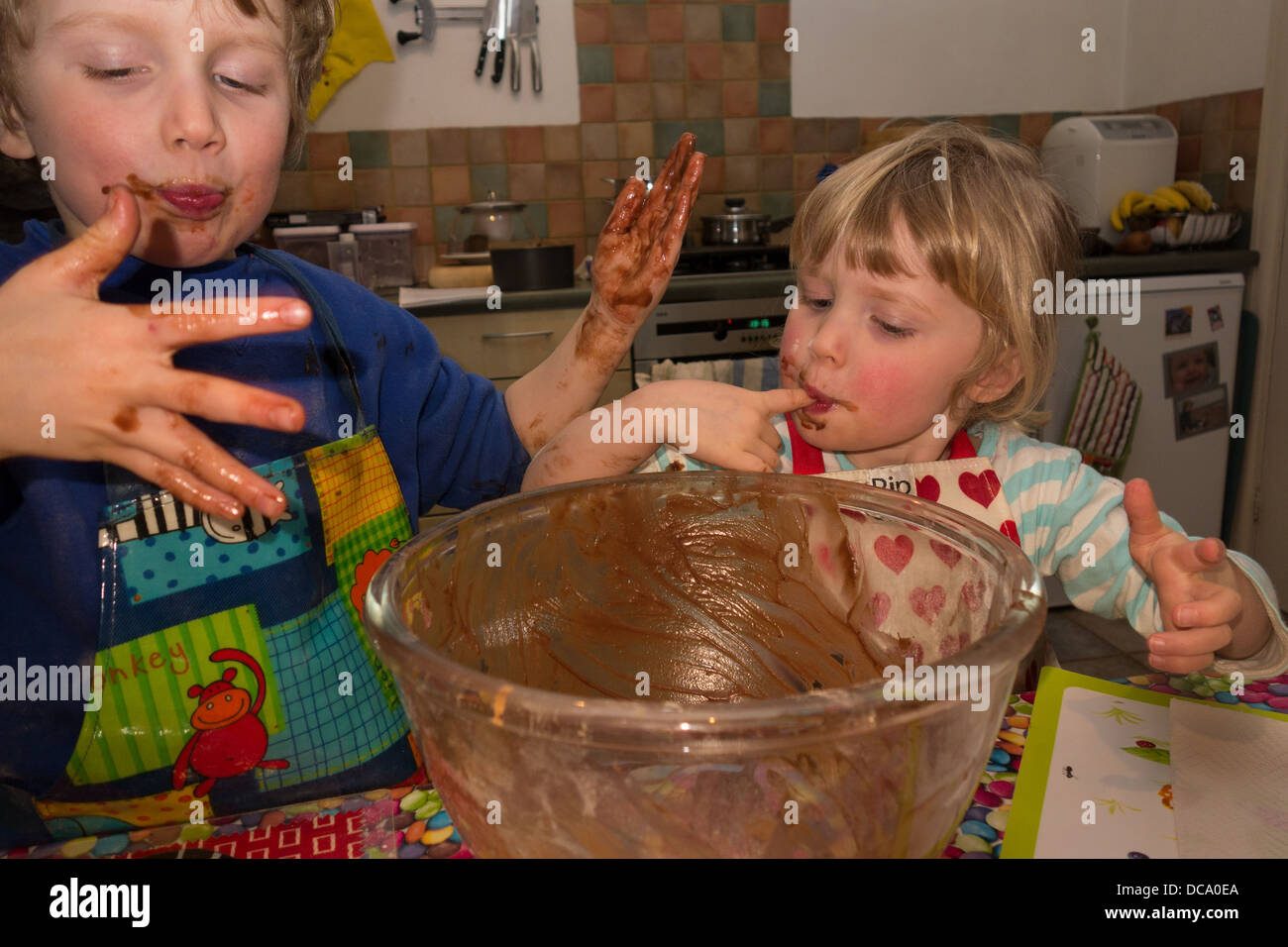 A pretty blond boy and girl savouring and licking  batter from their sticky fingers whilst enjoying baking a chocolate - Stock Image