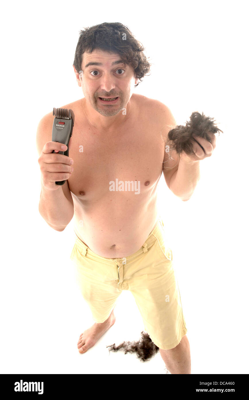 shirtless man with a haircut machine - Stock Image