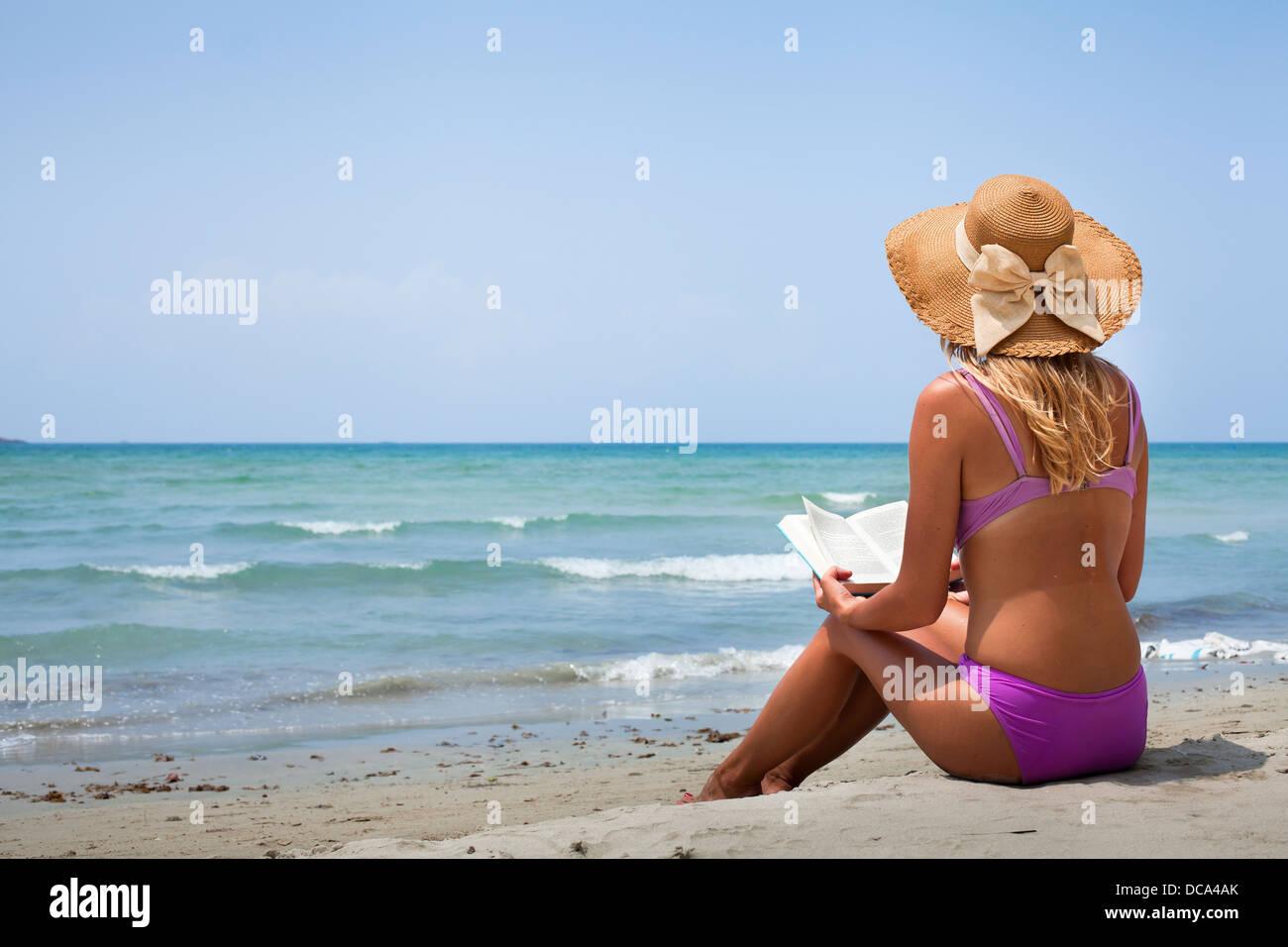 woman in bikini reading book on the beach - Stock Image