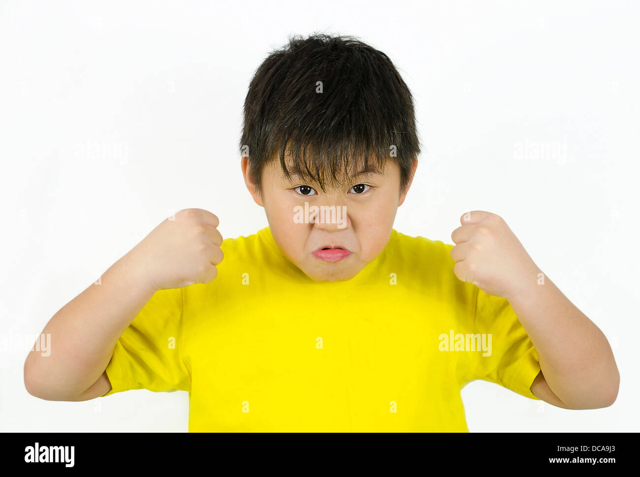 an angry child showing his temper and fists - Stock Image