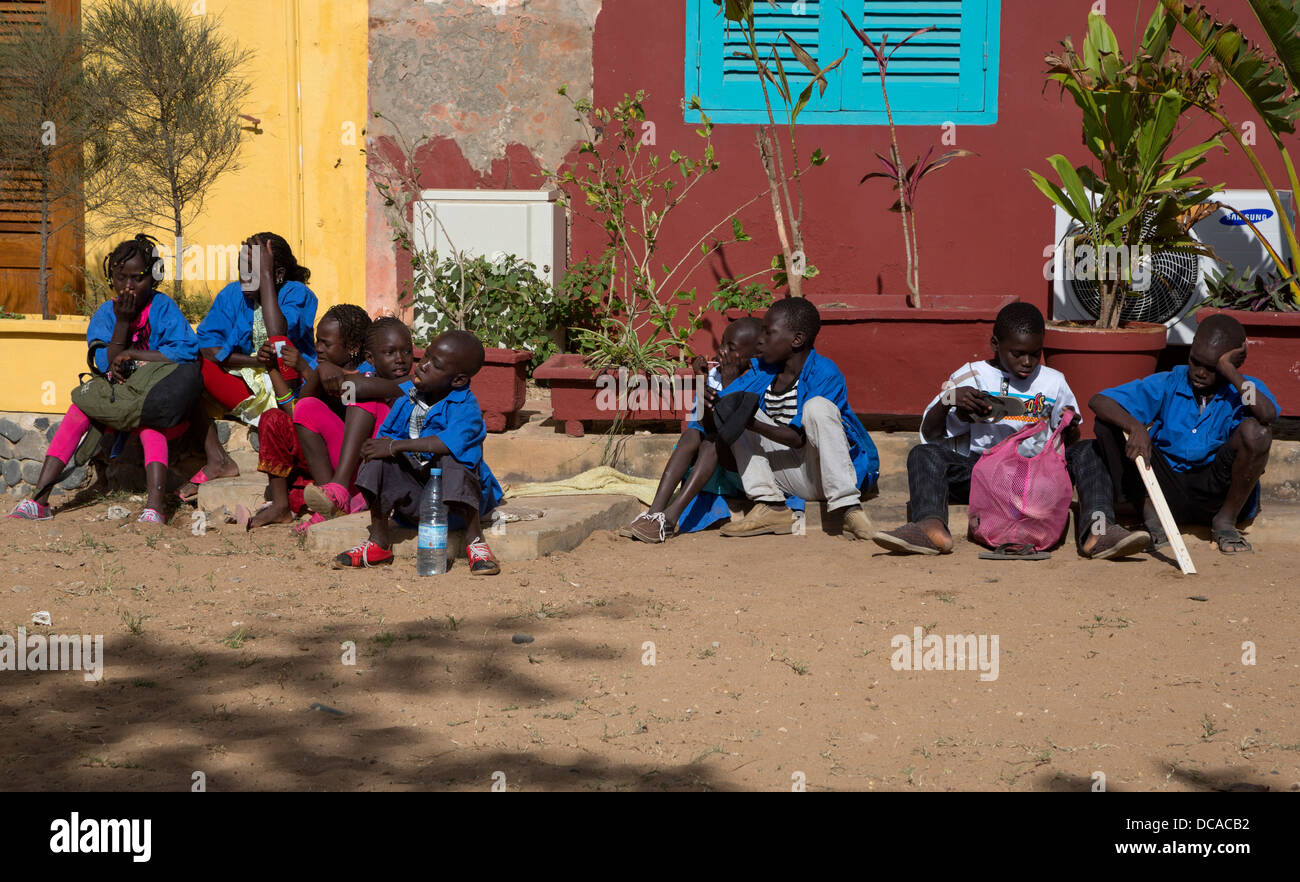 Senegalese School Children Waiting for a Group to Assemble, Goree Island, Senegal. - Stock Image