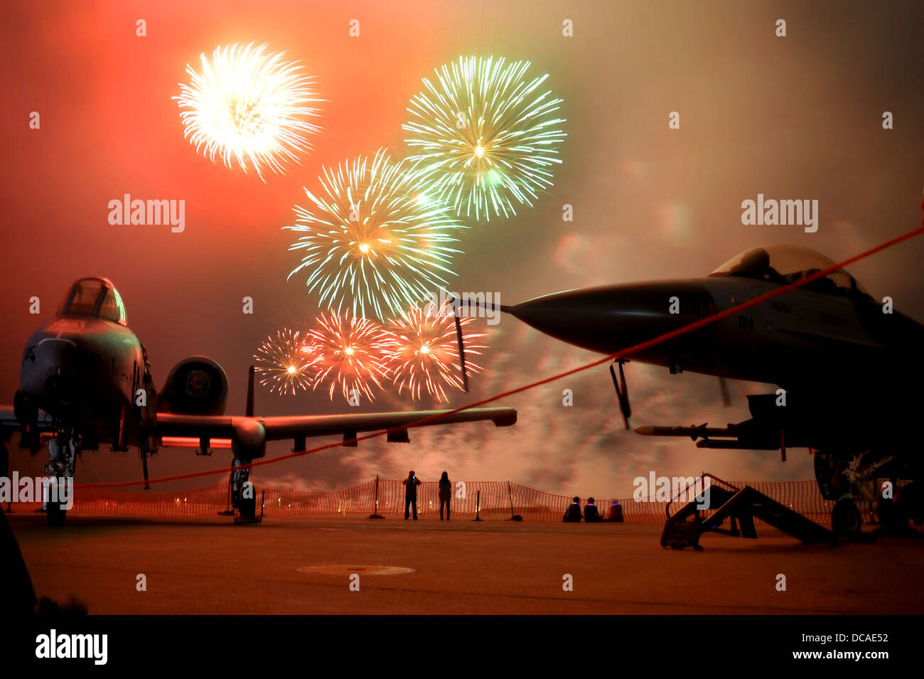 Fireworks erupt behind an A-10 Thunderbolt II and an F-16 Fighting Falcon during Liberty Fest celebration at Osan - Stock Image