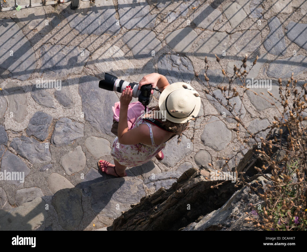 Woman photographer from above with a telephoto lens and a summer hat - Stock Image