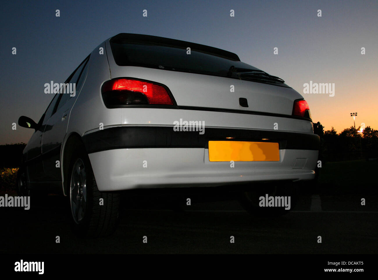 White Hatchback in sunset - Stock Image