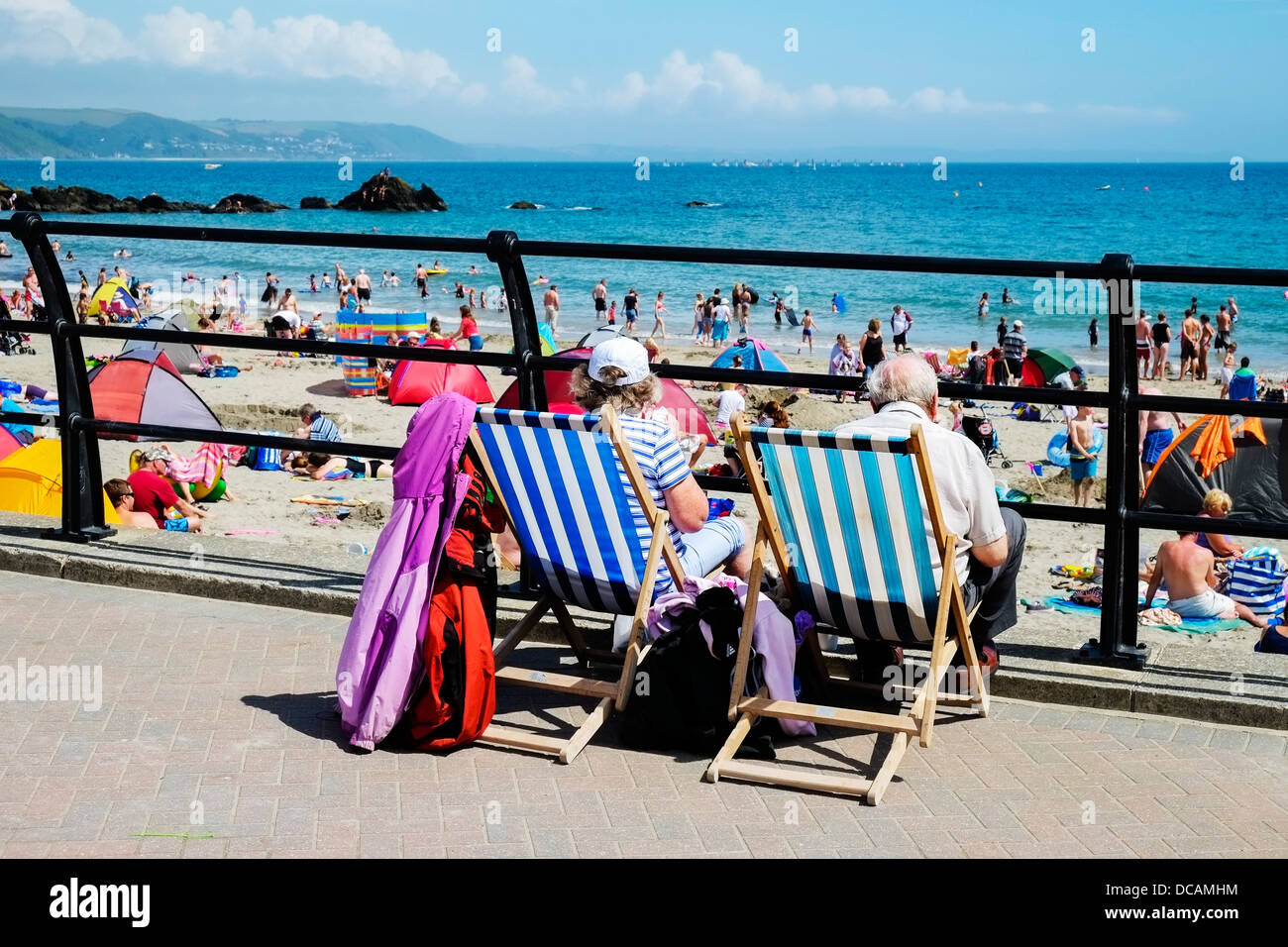 Looe in Cornwall - Holidaymakers sitting in deckchairs overlooking a busy and crowded East Looe Beach Cornwall UK - Stock Image