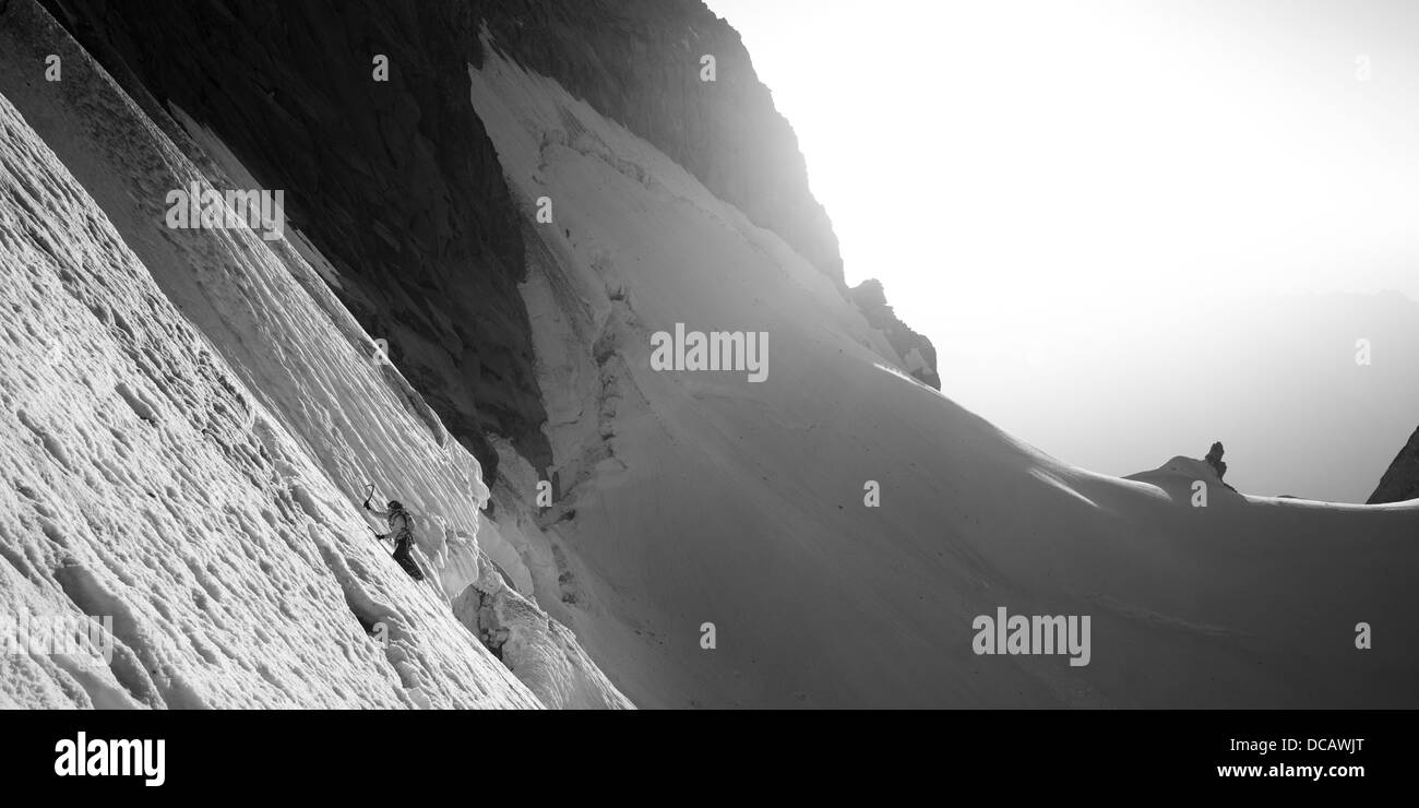 B&W panorama photography. Alpinist is climbing snow steep slope. Sunshine and snow crest is visible in background. - Stock Image