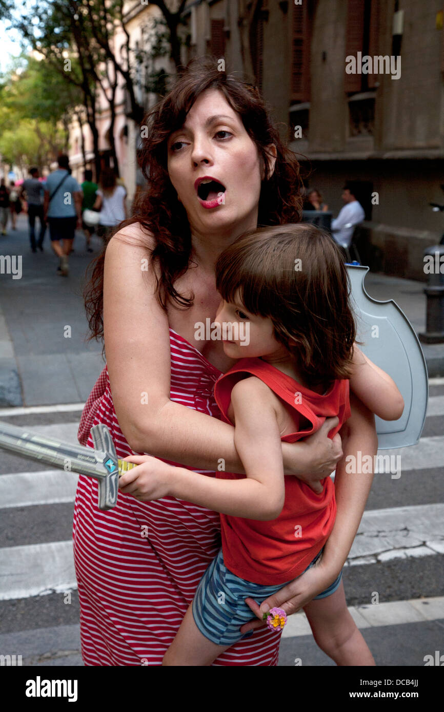 43 year old Spanish mother yelps in pain as she puts her four year old son down. - Stock Image