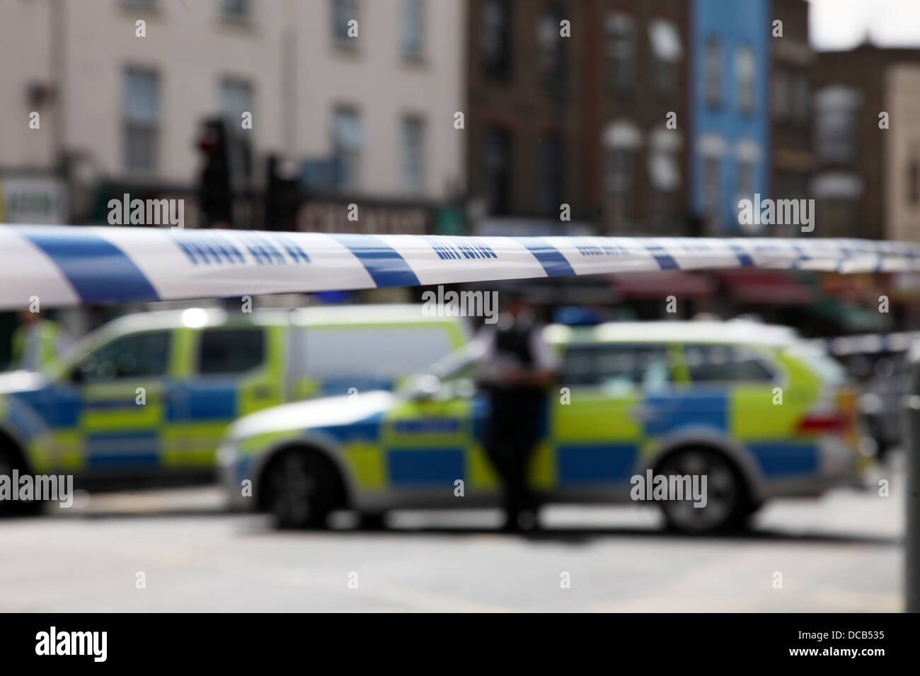 Police line with incident in the background and several police cars - Stock Image