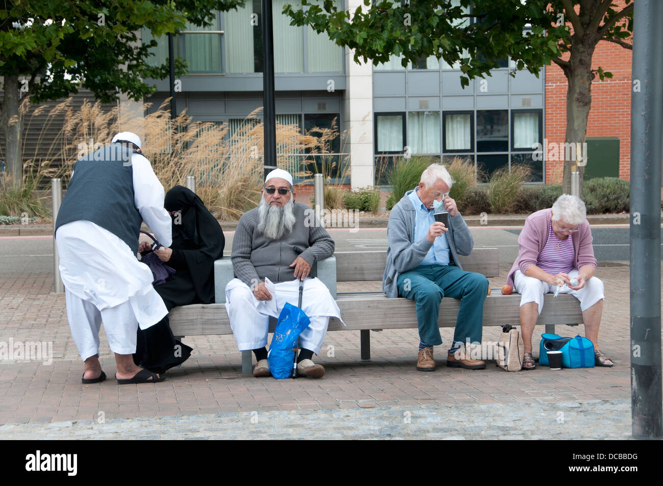Royal Docks, East London. Elderly couples , Muslim and white English, sitting on a bench - Stock Image