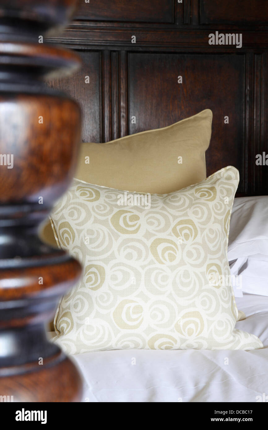 Detail of turned oak bed post, headboard panelling and cushions, Barnsley, UK. - Stock Image