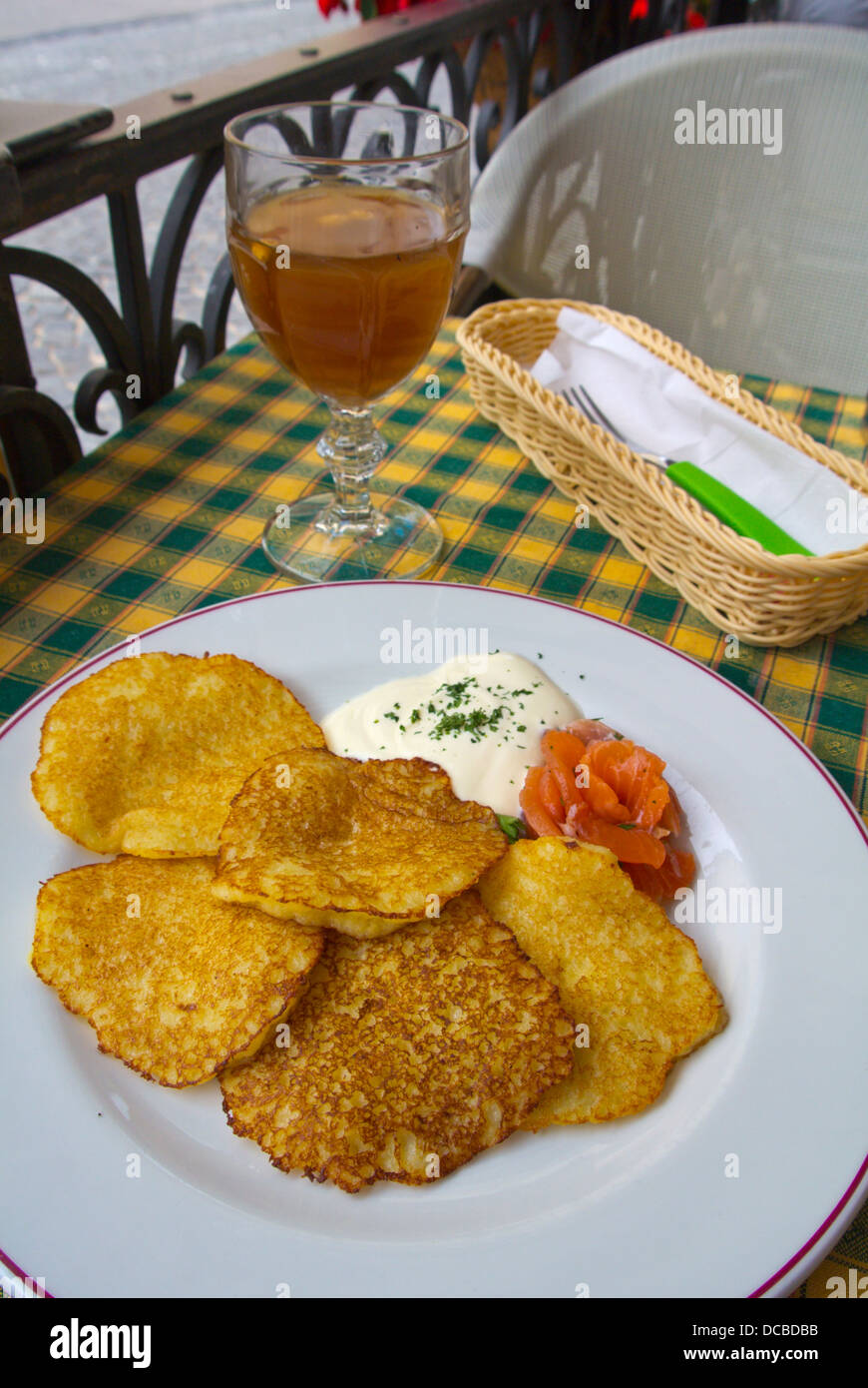 Local cuisine savory pancakes with salmon and kvass beverage in restaurant Vilnius Lithuania Europe - Stock Image