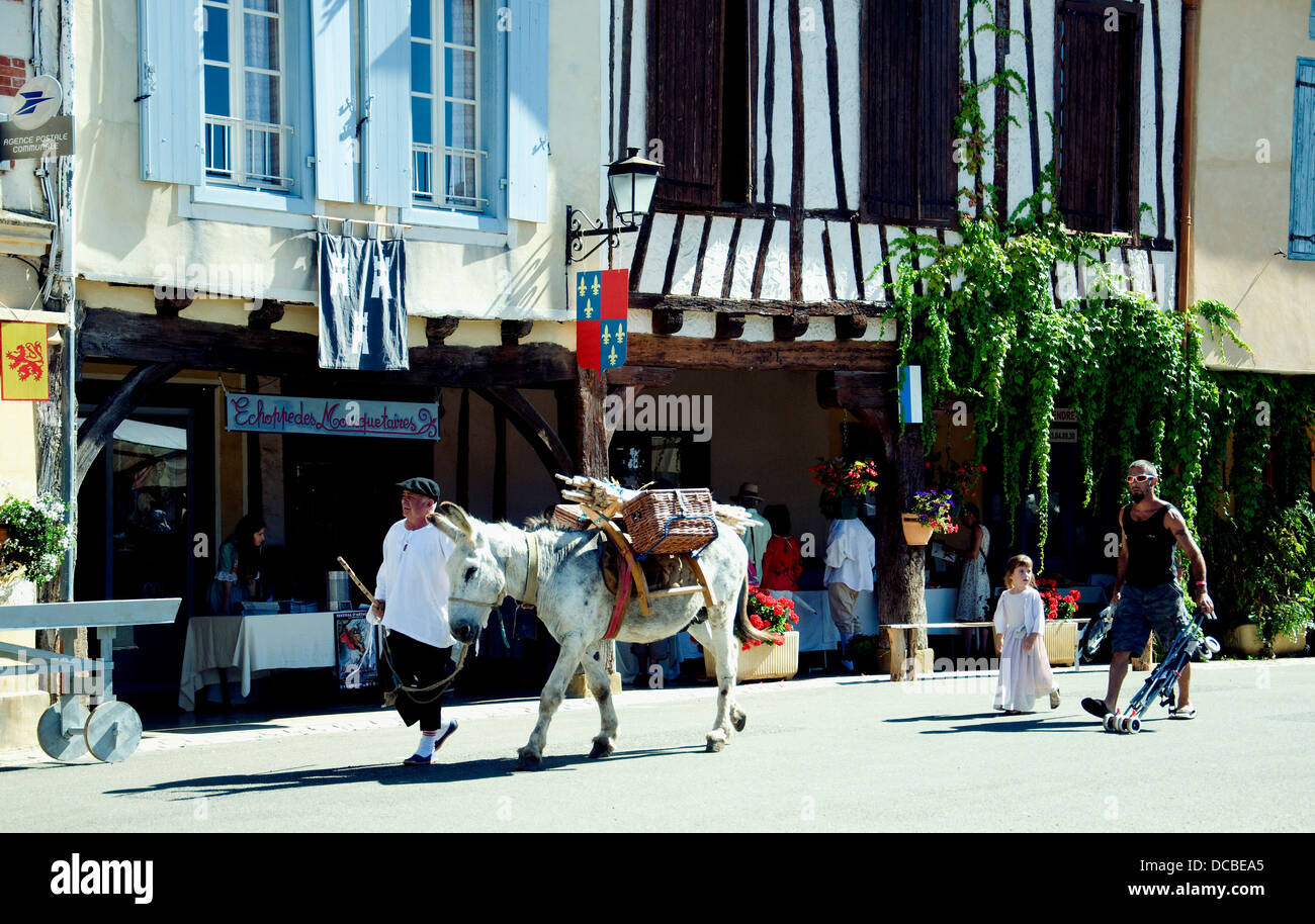 Dressed as rustic farmer, a man leads a donkey into the French village of Lupiac, a modern man with his daughter - Stock Image