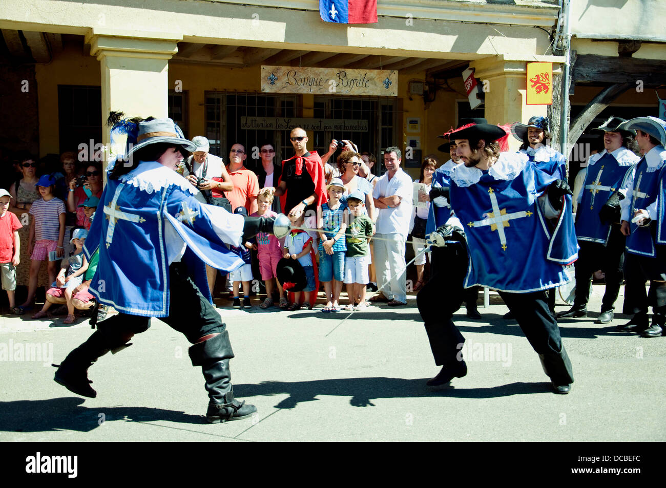 Dressed as Musketeers, young men mock duel in Lupiac, D'Artagnan's birthplace, during a fête honoring - Stock Image