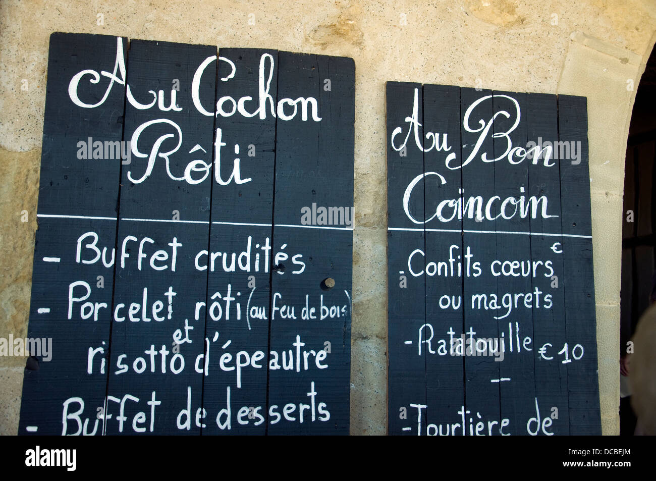 Time for lunch in Lupiac during the fête honoring native son D'Artagnan; roast piglet is prominent on one - Stock Image