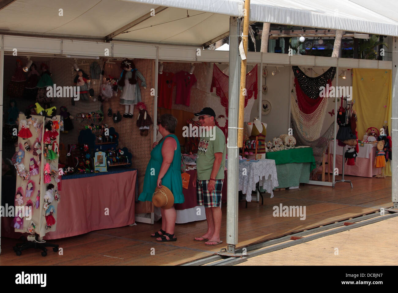 A couple visiting an open air, local arts and crafts fair. - Stock Image