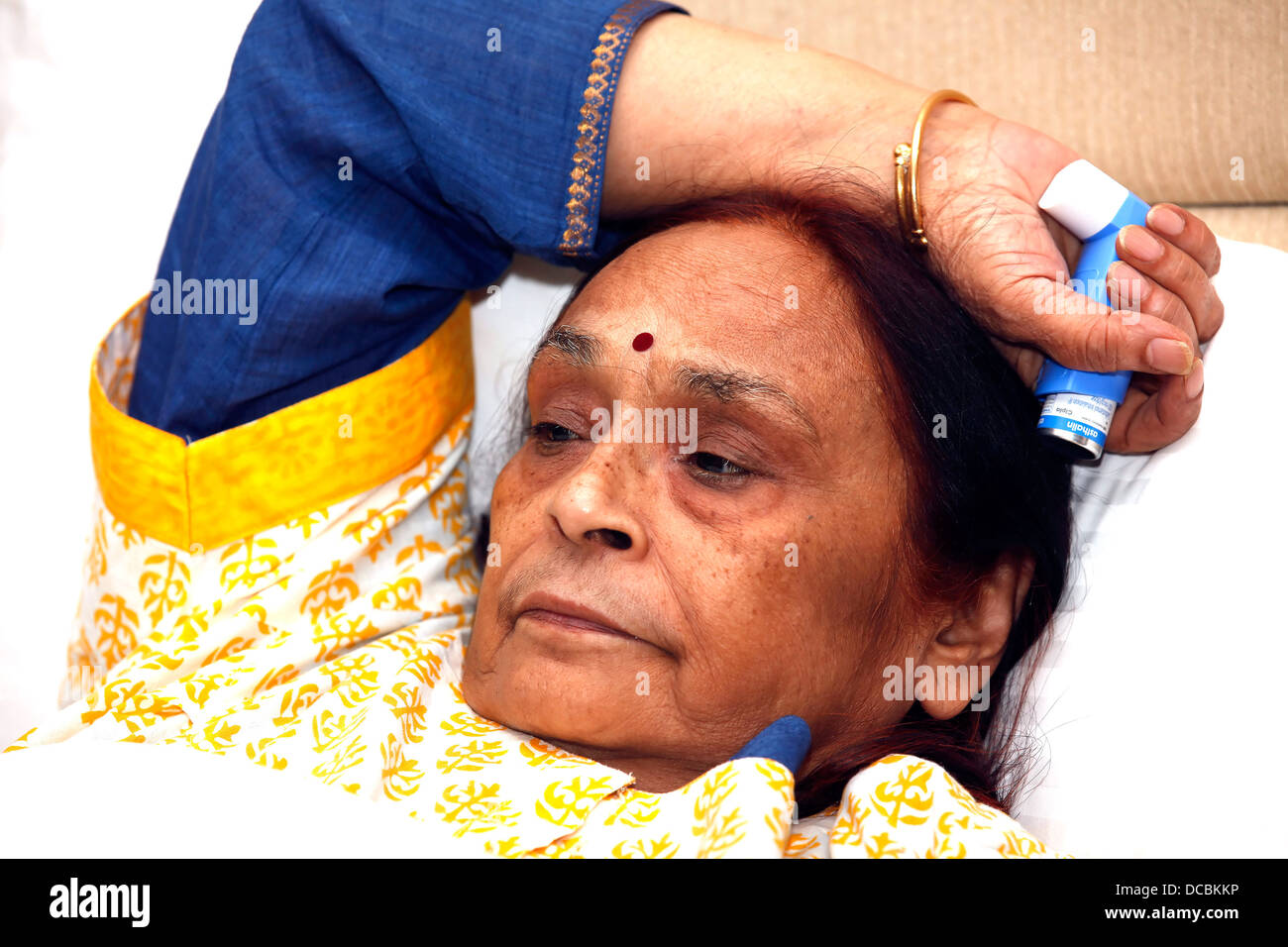Woman,Lady,elderly,patient,unwell,asthmatic,lying,bed-ridden,inhaler,ailing.respiratory problem,breathing problem,senior - Stock Image