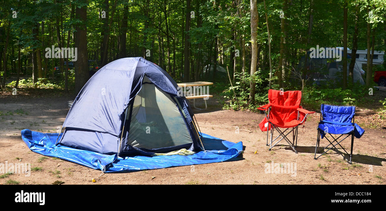 Campsite with chairs and tent among trees - Stock Image