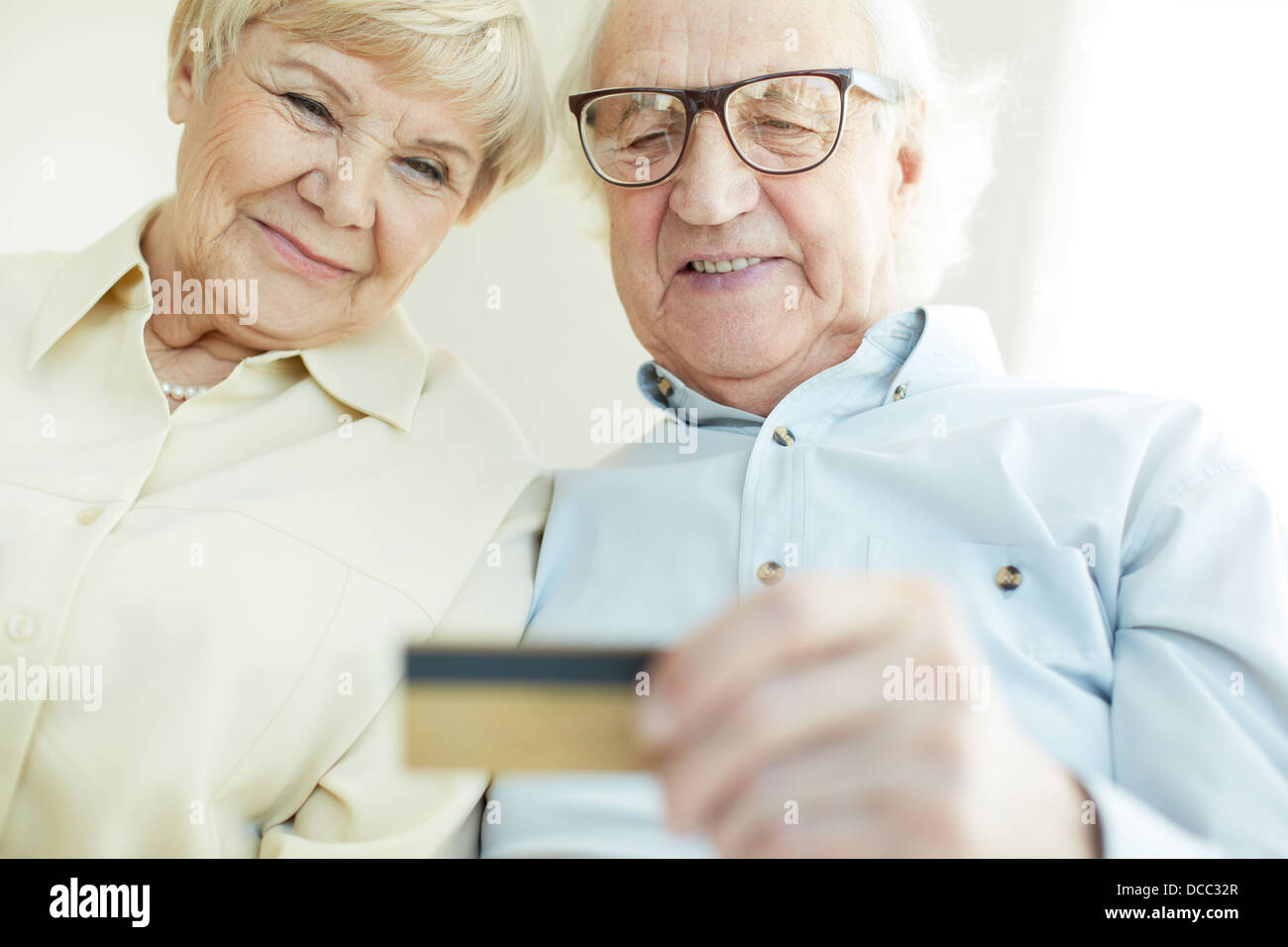 Portrait of elderly man and his wife looking at plastic card - Stock Image
