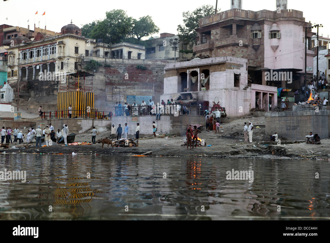 Mourners gather at the burning ghats on the banks of the RIver Ganges, Varanasi. - Stock Image