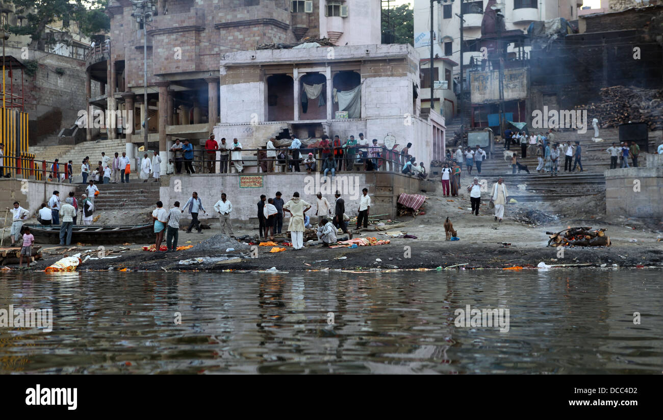 People gather at one of the burning ghats on the banks of the RIver Ganges in Varanasi, India - Stock Image