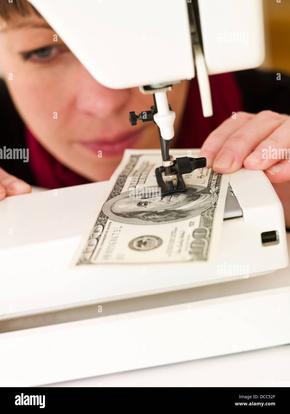 Woman sewing money - Stock Image