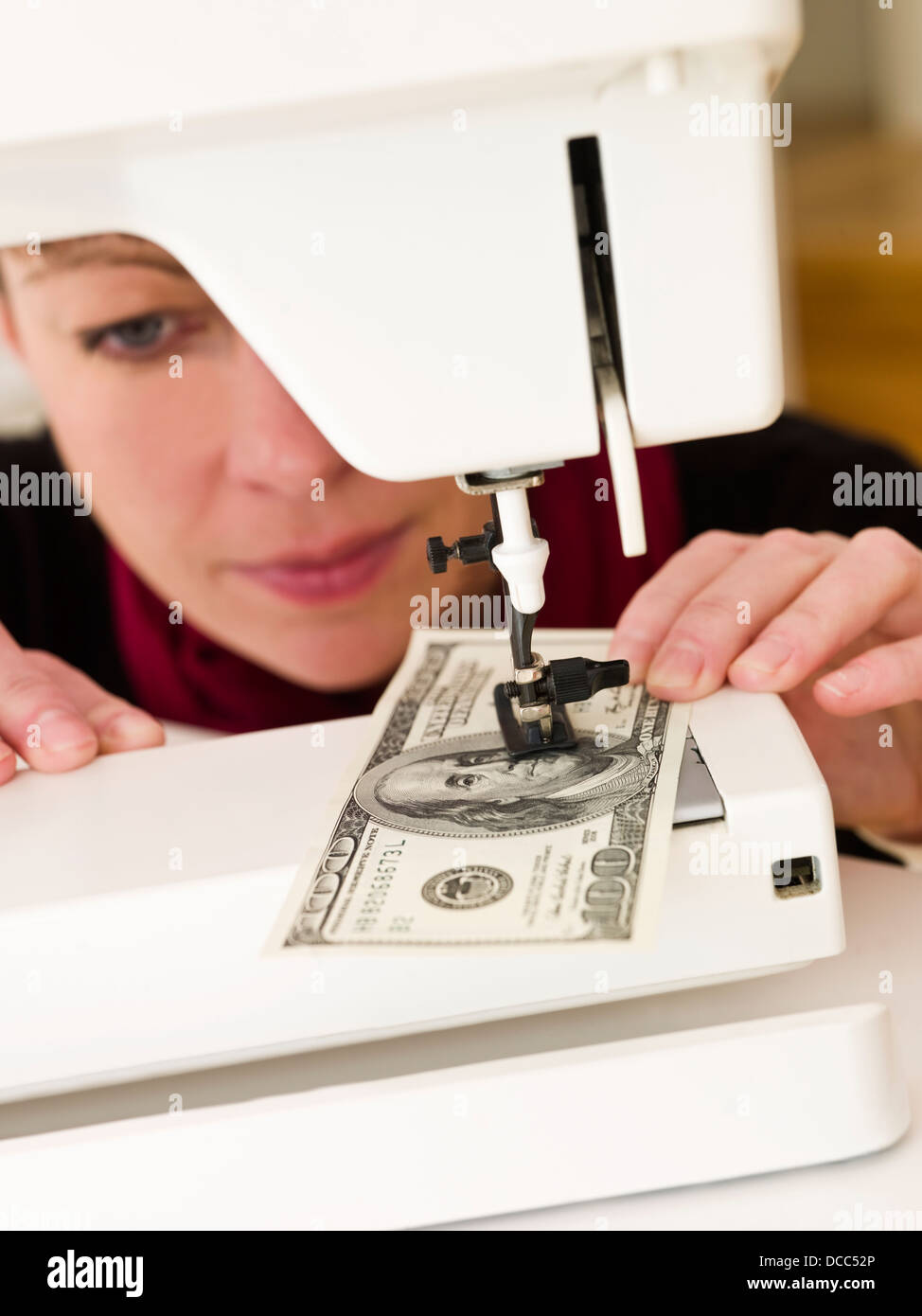 Woman sewing money Stock Photo