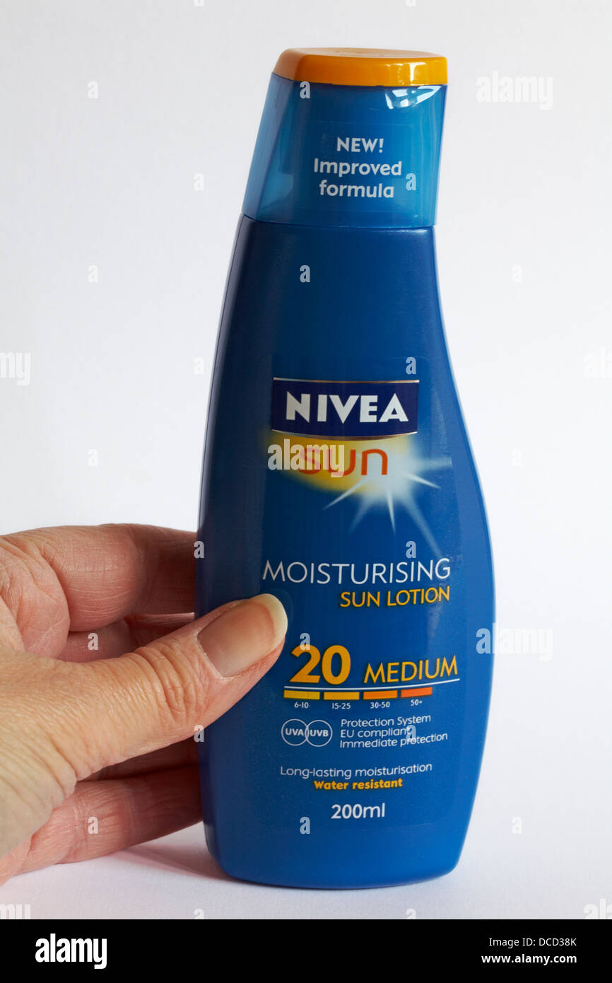 reaching for the Nivea Sun suntan lotion - Stock Image
