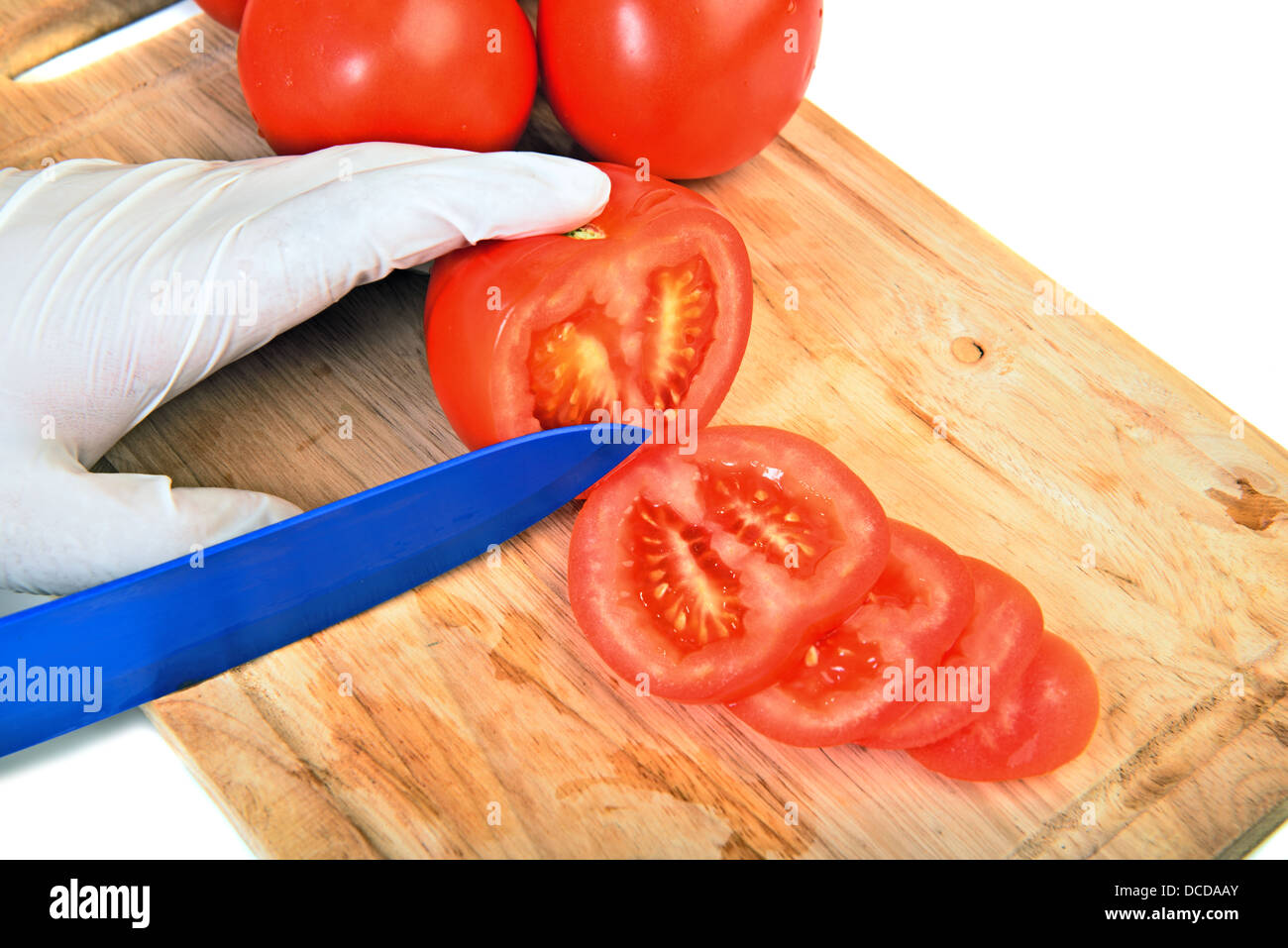 Slicing tomato on cutting board with ceramic knife over white - Stock Image