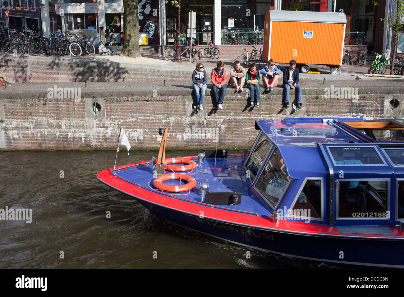 Group of young people watching boat tour along the Korte Prinsengracht canal in Amsterdam, Holland, Nentherlands. - Stock Image