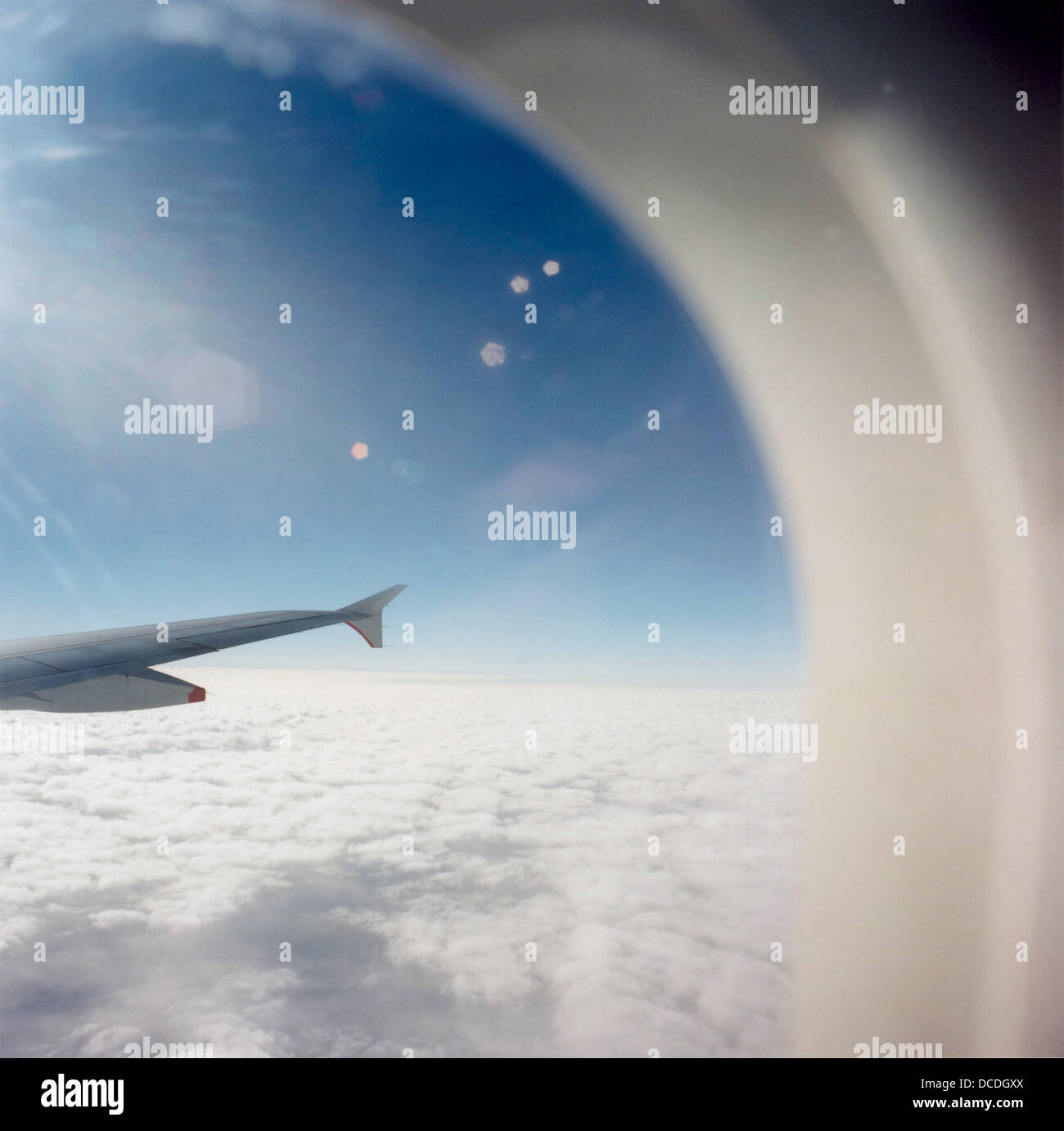 From an airliner passenger seat, bright sunshine causes lens flare during a flight across the English Channel between - Stock Image