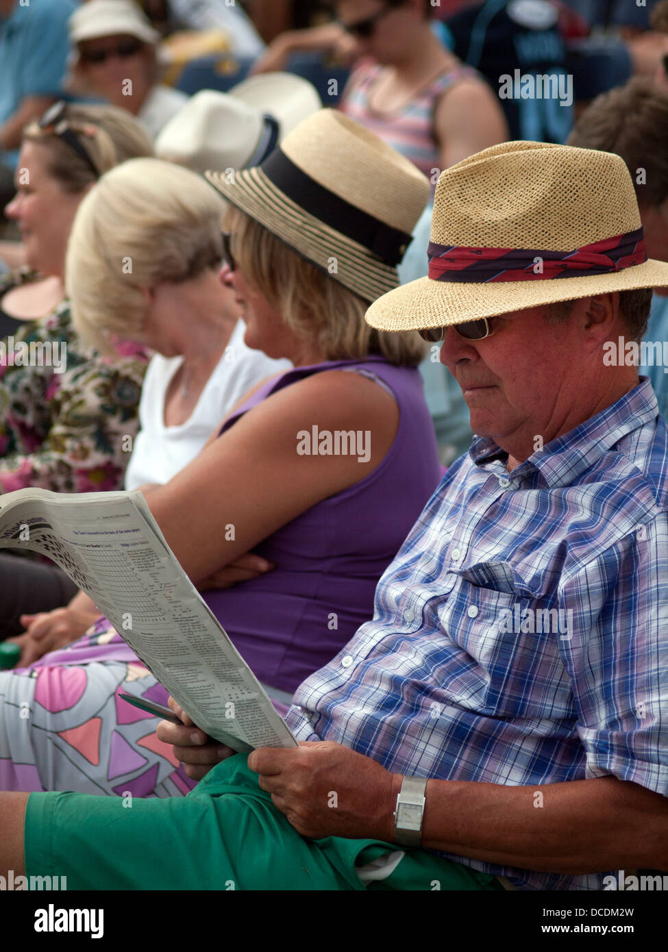 Reading a newspaper at a cricket match Stock Photo