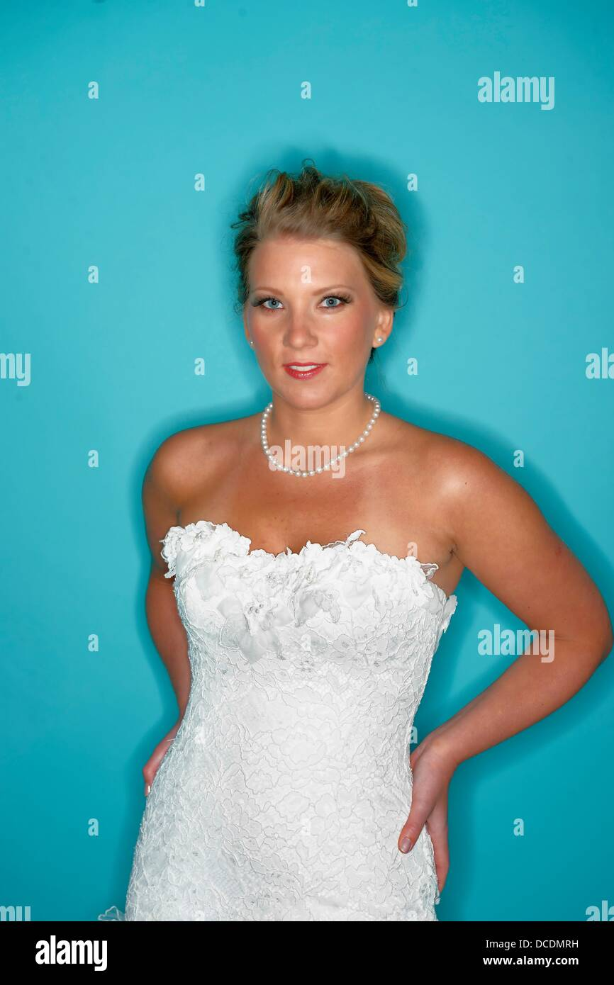 Bride in wedding dress shot with ring flash against blue background ...
