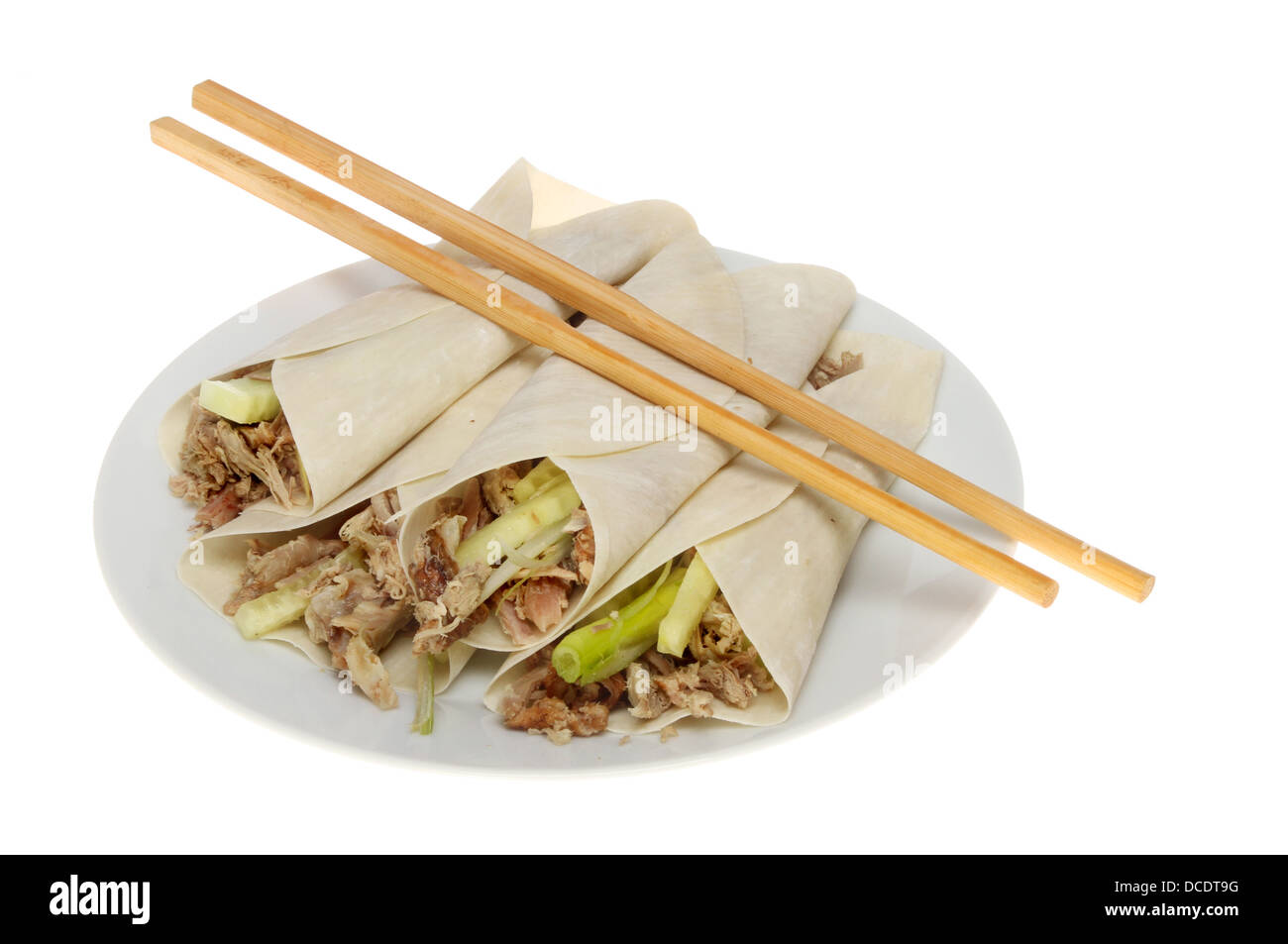 Chinese crispy duck pancakes with chopsticks on a plate isolated against white - Stock Image