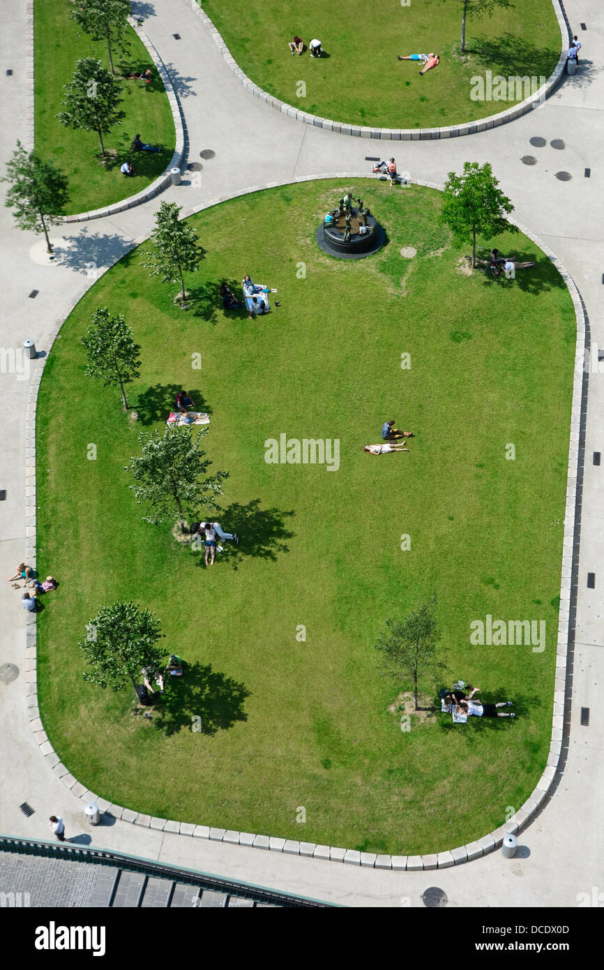 Aerial view on people sunning and sitting in the shadow of trees in small green city park on a hot day in summer, - Stock Image