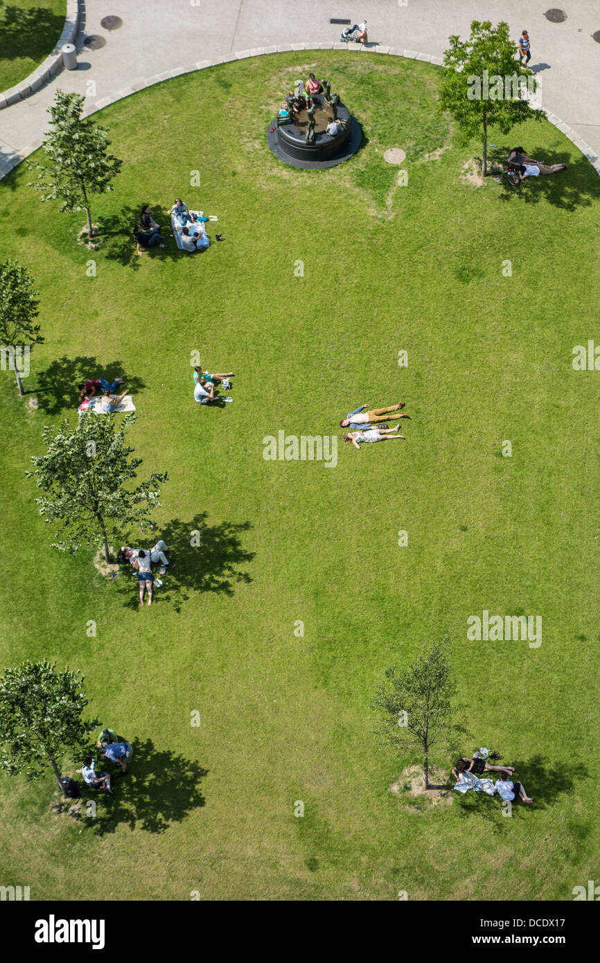 Aerial view on people sunning and sitting in the shadow of trees in little green city park on a hot day in summer - Stock Image