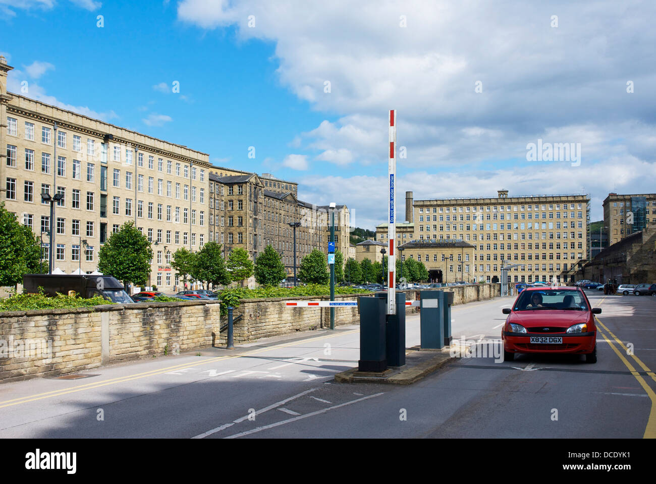 Car going through raised barrier to leave the car park of Dean Clough Mills, Halifax, West Yorkshire, England UK - Stock Image