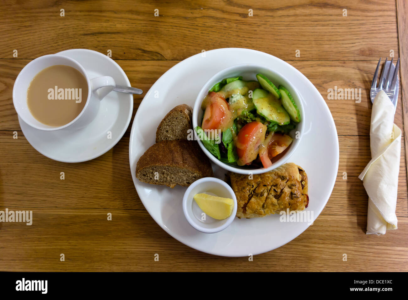 Bistro lunch sausage roll dressed salad artisan bread butter and tea - Stock Image